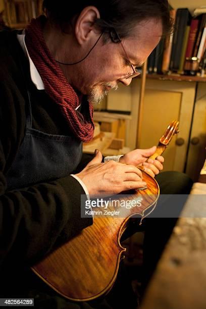 violin maker at work, polishing old violin