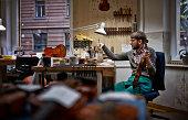Violin maker in his workshop varnishing repaired violin