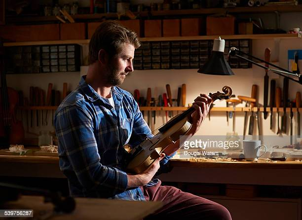 A violin maker looks over his workmanship.