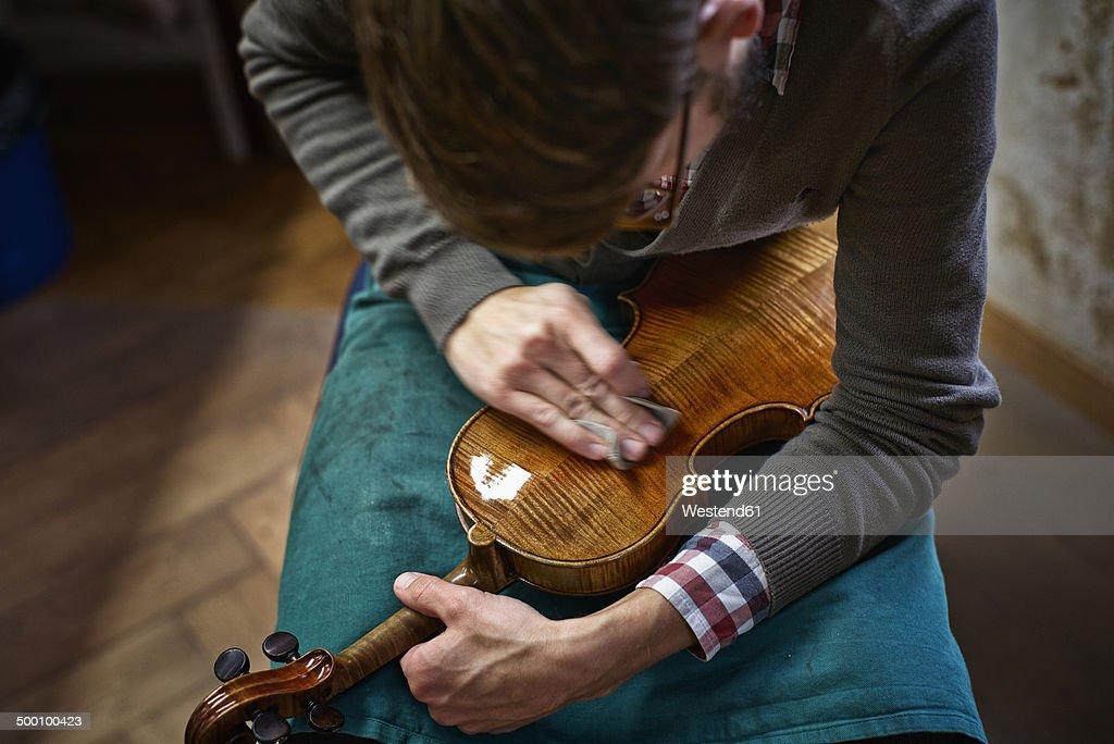 Violin maker polishing repaired violin