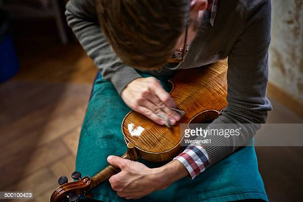 Violin maker polishing repaired violin
