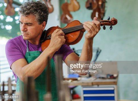 Violin Maker Testing an Instrument