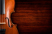 A violin on a grunge wooden board. The violin is lying on a dark red brown weathered wood table.