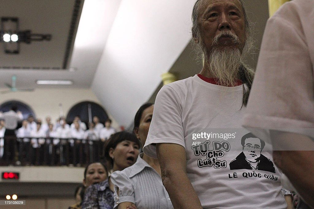 Violinist Chi Hai (2nd R) wears a T-shirt with portrait of democracy activist lawyer Le Quoc Quan as he attends a mass at a Catholic church in support of the lawyer Le Quoc Quan two days ahead of his trial in Hanoi on July 7, 2013. A prominent dissident lawyer, Le Quoc Quan who was arrested last December for 'tax evasion' charge will stand trial at a local court in Hanoi on July 9, 2013.