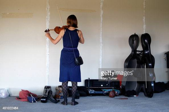 A violinist from the MultiStory Orchestra practices before a performance of Jean Sibelius' 5th Symphony at the Peckham Rye Car Park on June 21 2014...
