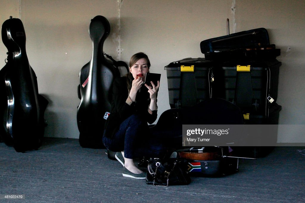 A violinist from the MultiStory Orchestra puts on her makeup ahead of a performance of Jean Sibelius' 5th Symphony in Peckham Rye car park on June 21...