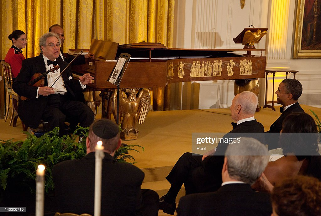 Violinist Itzhak Perlman (L) performs for U.S. President Barack Obama (R) and Israeli President Shimon Peres (2nd R) during a dinner in honor of Peres receiving the Presidential Medal of Freedom, in the East Room of the White House, on June 13, 2012 in Washington, D.C. Peres is the second Israeli, after Natan Sharansky, to receive the Presidential Medal of Freedom.