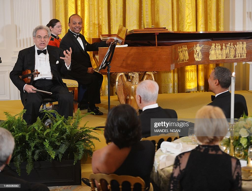 Violinist Itzhak Perlman (L) speaks before performing at a dinner honouring Israeli President Shimon Peres (2nd R) as US President Barack Obama (R) looks on June 13, 2012 in the East Room of the White House in Washington, DC. AFP PHOTO/Mandel NGAN