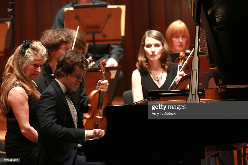 Violinist Jacqueline Shave looks on as English pianist Benjamin Grosvenor directs while playing the piano the Britten Sinfonia in a performance of Mozart's last piano concerto at Milton Court Concert Hall on May 1, 2016 in London, England.