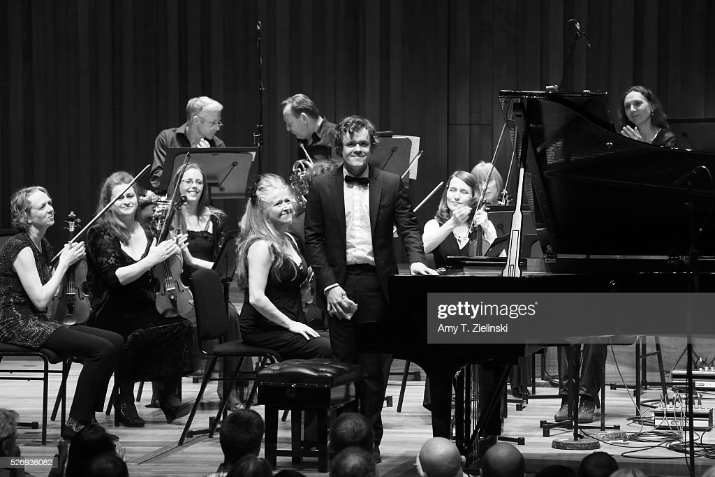 Violinist Jacqueline Shave looks on as English pianist Benjamin Grosvenor receives the audience after directing while playing the piano with the Britten Sinfonia in a performance of Mozart's last piano concerto at Milton Court Concert Hall on May 1, 2016 in London, England.