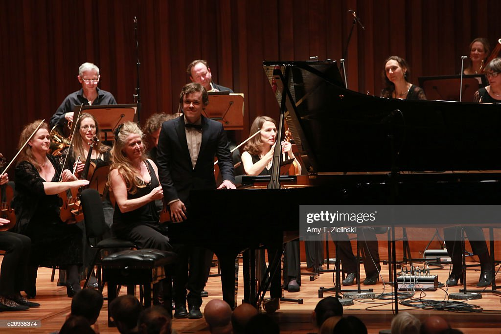 Violinist Jacqueline Shave looks on as English pianist Benjamin Grosvenor receives the audience before directing while playing the piano with the Britten Sinfonia in a performance of Mozart's last piano concerto at Milton Court Concert Hall on May 1, 2016 in London, England.