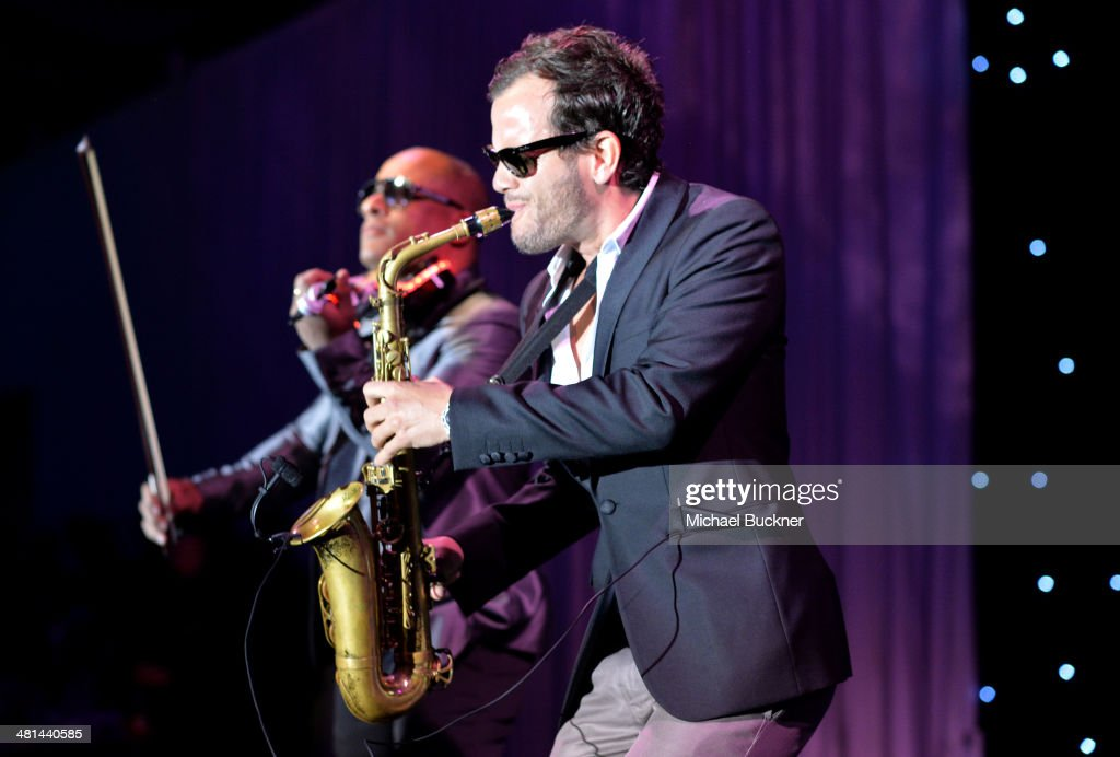 Violinist Julio Cuba and saxophonist Florencio Cruz perform onstage during MOCA's 35th Anniversary Gala presented by Louis Vuitton at The Geffen Contemporary at MOCA on March 29, 2014 in Los Angeles, California.