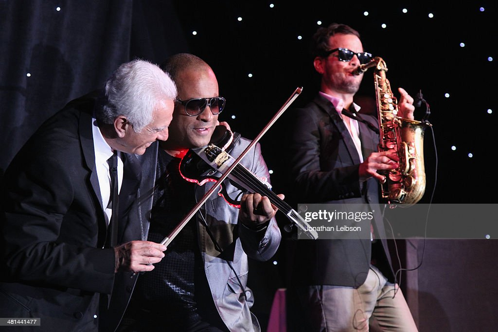 Violinist Julio Cuba and saxophonist Florencio Cruz (R) perform onstage during MOCA's 35th Anniversary Gala presented by Louis Vuitton at The Geffen Contemporary at MOCA on March 29, 2014 in Los Angeles, California.
