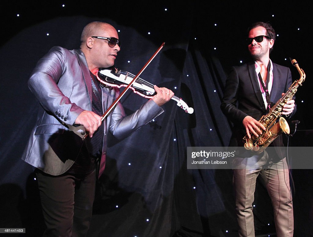Violinist Julio Cuba and saxophonist Florencio Cruz (R) performs during MOCA's 35th Anniversary Gala presented by Louis Vuitton at The Geffen Contemporary at MOCA on March 29, 2014 in Los Angeles, California.