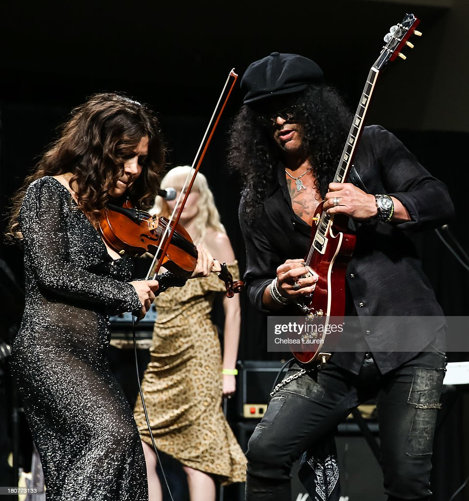 Violinist <a gi-track='captionPersonalityLinkClicked' href=/galleries/search?phrase=Lili+Haydn&family=editorial&specificpeople=839926 ng-click='$event.stopPropagation()'>Lili Haydn</a> (L) and guitarist Slash perform at Adopt the Arts' Peace Through Music celebrity gala at Loews Hollywood Hotel on September 15, 2013 in Hollywood, California.