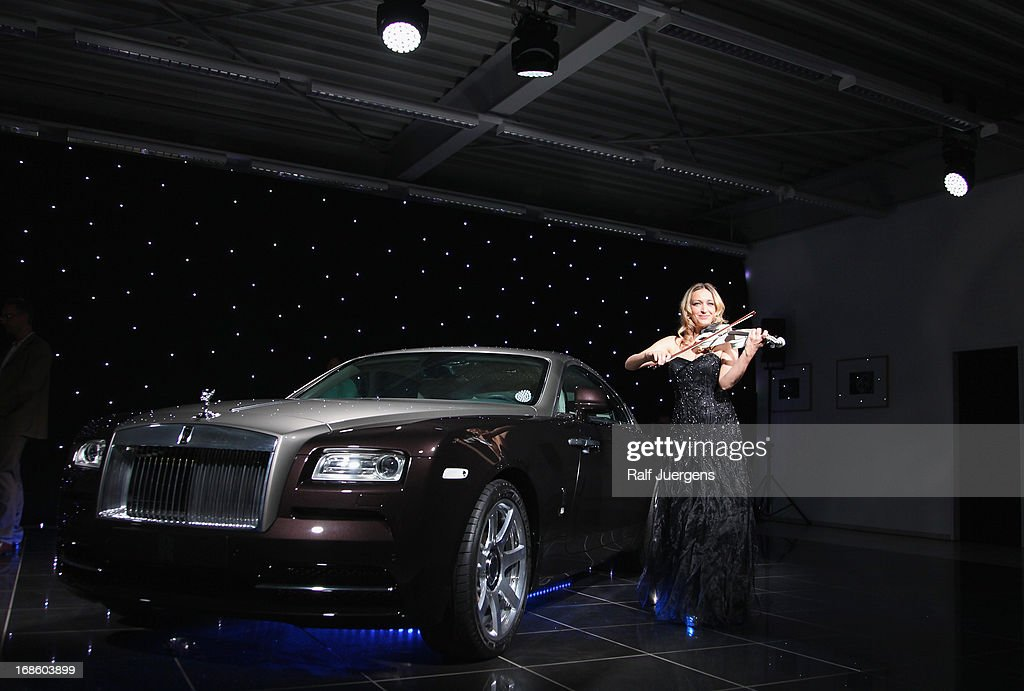 Violinist Luciana Beleaeva performs next to the new Rolls Royce Wraith which is displayed for the first time in Germany at 'Procar-Automobile' on May 11, 2013 in Cologne, Germany.