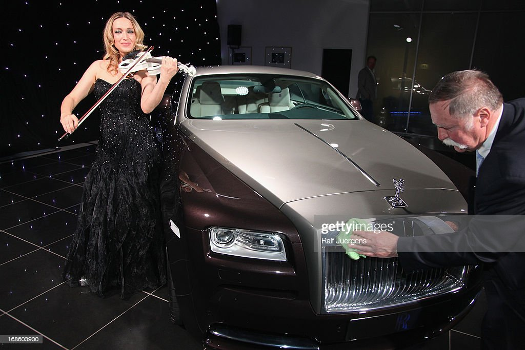 Violinist Luciana Beleaeva (L) performs next to the new Rolls Royce Wraith which is displayed for the first time in Germany at 'Procar-Automobile' on May 11, 2013 in Cologne, Germany.