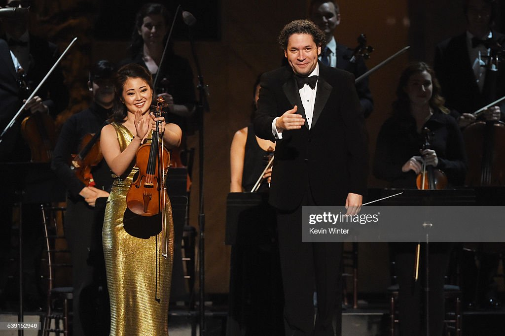 Violinist Simone Porter (L) and conductor Gustavo Dudamel perform onstage during American Film Institute's 44th Life Achievement Award Gala Tribute to John Williams at Dolby Theatre on June 9, 2016 in Hollywood, California. 26148_004