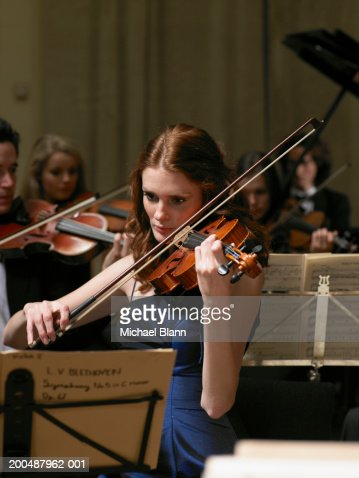 Violinists performing in orchestra, focus on woman in foreground : Stock Photo