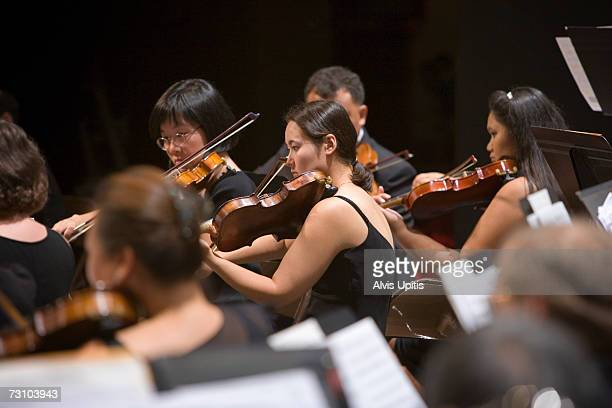 Violins performing in symphony orchestra