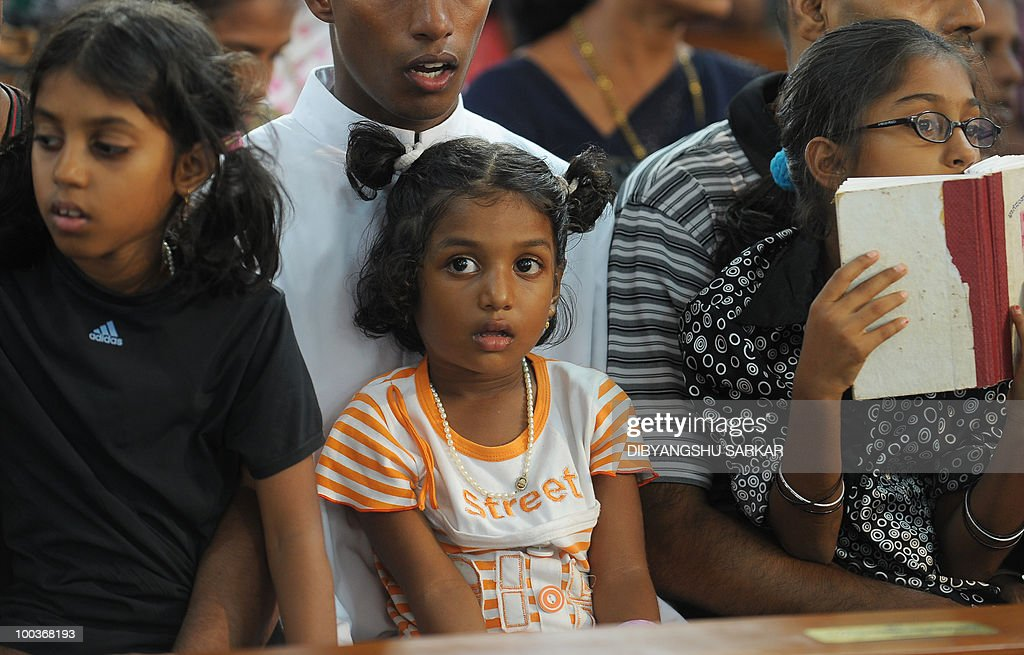 Violla (C), the four-year old daughter of Air India Express crash victims Naveen Walton Fernandes and Savitha Philomene D'Souza, attends her parents' funeral service at the Holly Cross Church in Mangalore on May 24, 2010. Investigators on May 22 widened the search for the 'black box' data recorder of an Air India Express that crashed into a gorge killing 158 people, as the airline denied lax safety claims. AFP PHOTO/Dibyangshu SARKAR