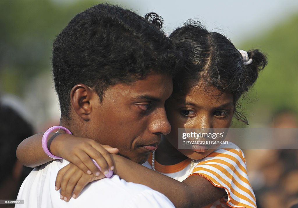 Violla (R), the four-year old daughter of Air India Express crash victims Naveen Walton Fernandes and Savitha Philomene D'Souza, looks on during the burial of her parents on the grounds of the Holly Cross Church in Mangalore on May 24, 2010. Investigators on May 22 widened the search for the 'black box' data recorder of an Air India Express that crashed into a gorge killing 158 people, as the airline denied lax safety claims. AFP PHOTO/Dibyangshu SARKAR