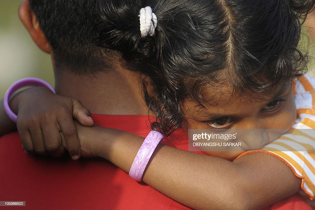Violla, the four-year old daughter of Air India Express crash victims Naveen Walton Fernandes and Savitha Philomene D'Souza, looks on while carried by a family member during the burial of her parents on the grounds of the Holly Cross Church in Mangalore on May 24, 2010. Investigators on May 22 widened the search for the 'black box' data recorder of an Air India Express that crashed into a gorge killing 158 people, as the airline denied lax safety claims. AFP PHOTO/Dibyangshu SARKAR