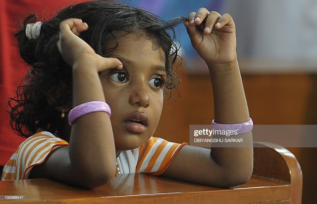 Violla, the four-year old daughter of Air India Express crash victims Naveen Walton Fernandes and Savitha Philomene D'Souza, attends her parents' funeral service at the Holly Cross Church in Mangalore on May 24, 2010. Investigators on May 22 widened the search for the 'black box' data recorder of an Air India Express that crashed into a gorge killing 158 people, as the airline denied lax safety claims. AFP PHOTO/Dibyangshu SARKAR