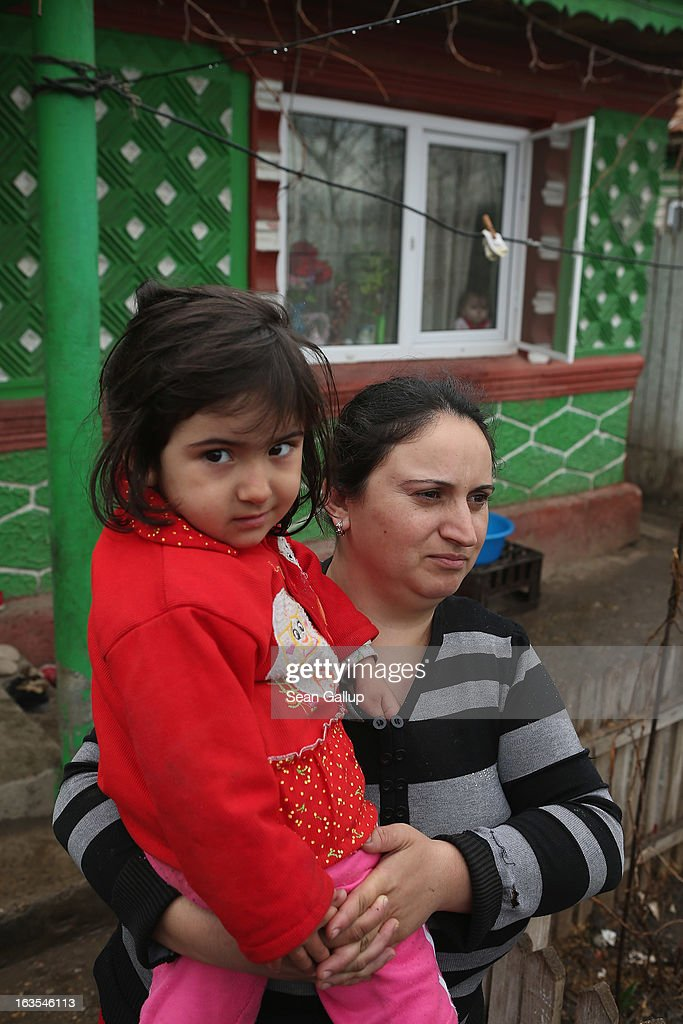 Viorica Gheorghe, who is an ethnic Roma, holds her daughter Gabriela, 3, outside their home on March 11, 2013 in Dilga, Romania. Viorica's husband works in Bucharest, a two-hour train commute away, and the couple, their two children and his mother surive on his salary of EUR 200 a month. Dilga is a settlement of 2,500 people with dirt roads and no running water, and unemployment is at 70%. Most of the working-age men and women have at some point worked abroad, mostly in Italy or Great Britain, as many say they are unable to find adequate work in Romania. Romania's Roma belong to a myriad of different tribes defined by their craft, and Dilga's belong to a group called the Rudari, who until the 1930s specialised in woodcrafts. During the communist years most worked in nearby state-run factories and agricultural cooperatives, though the majority of these went bankrupt after 1989 and the local Roma lost their jobs. Since then they have struggled to make ends meet and find a better future for their children, though projects initiated by the European Union and NGOs are helping some to launch small-scale enterprises and improve their children's education.