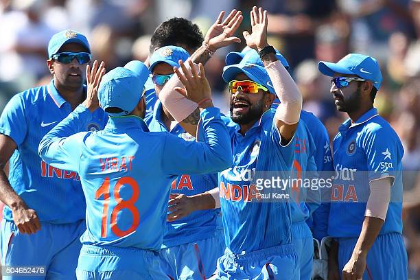 Virat Kholi and Shikhar Dhawan of India celebrate the wicket of David Warner of Australia during the Victoria Bitter One Day International Series...