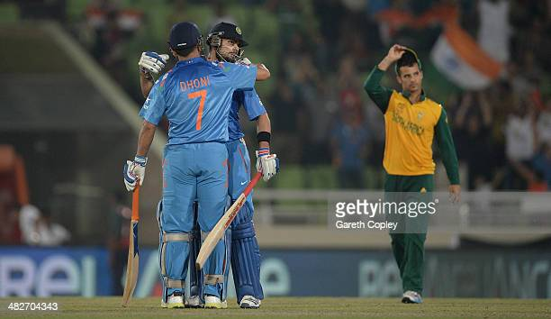 Virat Kohli and Mahendra Singh Dhoni of India celebrate winning the ICC World Twenty20 Bangladesh 2014 semi final between India and South Africa at...