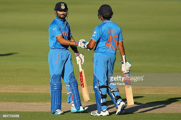 Virat Kohli and Rohit Sharma of India celebrate 50 runs during the 2015 ICC Cricket World Cup match between India and the United Arab Emirates at...