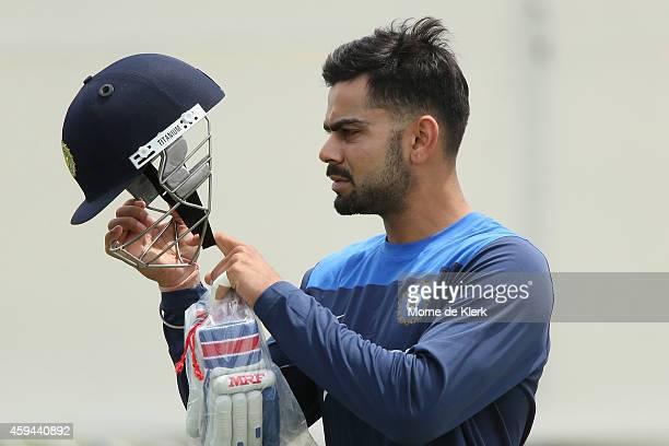 Virat Kohli inspects his helmet during a training session for the Indian cricket team at Gliderol Stadium on November 23 2014 in Adelaide Australia