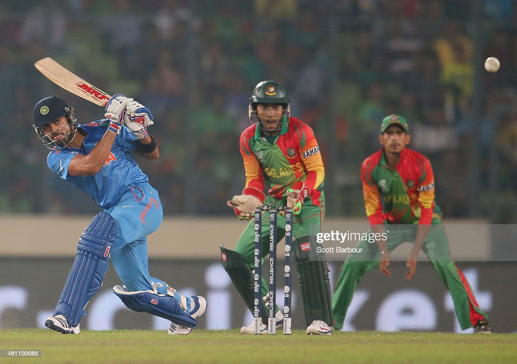 Virat Kohli of India bats as Mushfiqur Rahim of Bangladesh looks on during the ICC World Twenty20 Bangladesh 2014 match between Bangladesh and India at Sher-e-Bangla Mirpur Stadium on March 28, 2014 in Dhaka, Bangladesh.