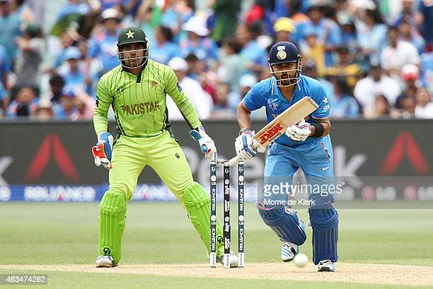 Virat Kohli of India bats in front of Umar Akmal of Pakistan during the 2015 ICC Cricket World Cup match between India and Pakistan at Adelaide Oval...