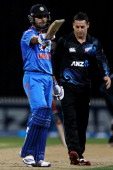 Virat Kohli of India celebrates his half century as Nathan McCullum of New Zealand looks on during the One Day International match between New...