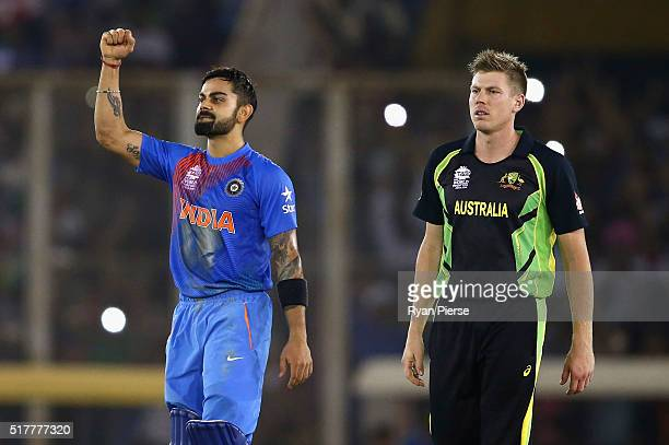 Virat Kohli of India celebrates victory as James Faulkner of Australia looks on during the ICC WT20 India Group 2 match between India and Australia...