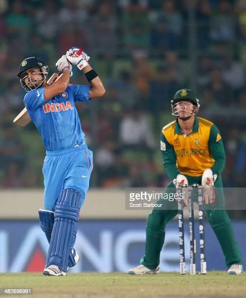 Virat Kohli of India hits a six as Quinton de Kock of South Africa looks on during the ICC World Twenty20 Bangladesh 2014 2nd SemiFinal match between...