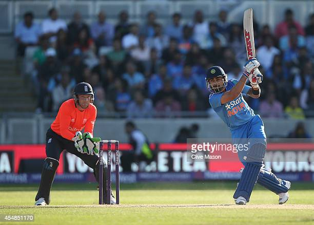 Virat Kohli of India hits out as Jos Buttler of England looks on during the NatWest International T20 2014 match between England and India at...