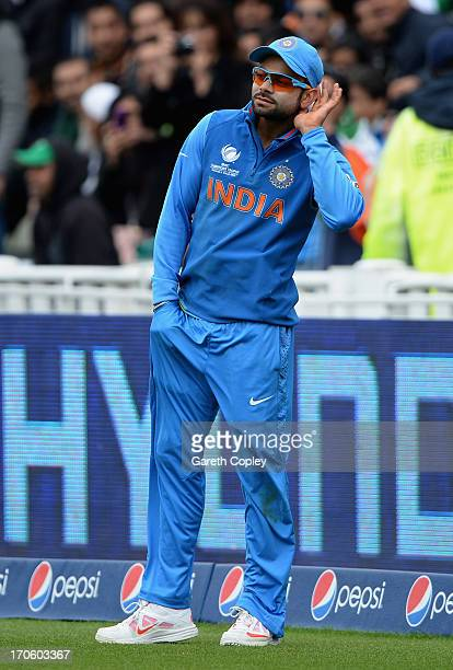 Virat Kohli of India holds his hand to his ear to listen to Pakistan fans chants during the ICC Champions Trophy match between India and Pakiatan at...