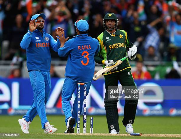 Virat Kohli of India is congratulated by Suresh Raina after running out Junaid Khan of Pakistan during the ICC Champions Trophy Group A match between...