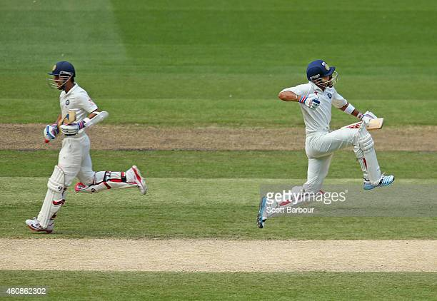 Virat Kohli of India leaps as he celebrates after reaching his century as Ajinkya Rahane runs between the wickets during day three of the Third Test...