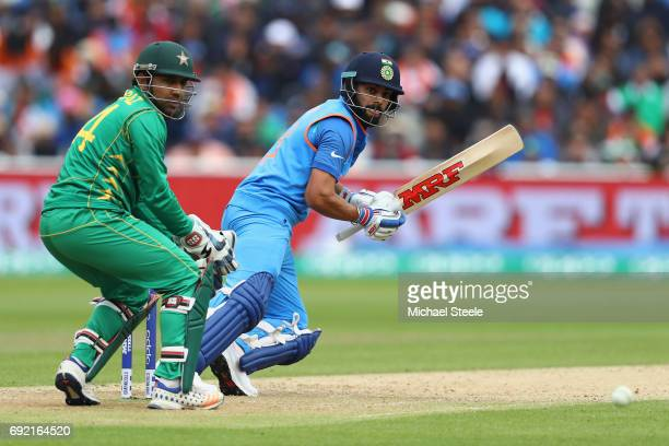 Virat Kohli of India plays behind point as Pakistan wicketkeeper Sarfraz Ahmed looks on during the ICC Champions Trophy match between India and...