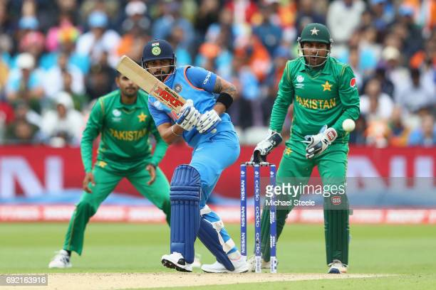 Virat Kohli of India plays to the offside as Pakistan wicketkeeper Sarfraz Ahmed looks on during the ICC Champions Trophy match between India and...