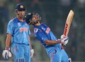 Virat Kohli of India screams after he hit the winning runs as MS Dhoni looks on as India win the ICC World Twenty20 Bangladesh 2014 2nd SemiFinal...