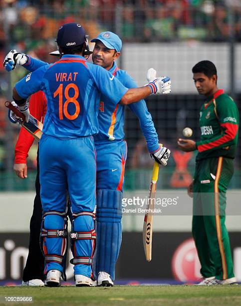 Virender Sehwag of India celebrates with team mate Virat Kohli on reaching his century during the opening game of the ICC Cricket World Cup between...