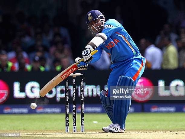 Virender Sehwag of India cover drives for four during the 2011 ICC World Cup Group B match between India and England at M Chinnaswamy Stadium on...