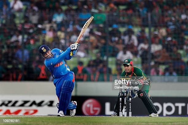 Virender Sehwag of India hits a six as wicketkeeper Mushfiqur Rahim of Bangladesh looks on during the opening game of the ICC Cricket World Cup...