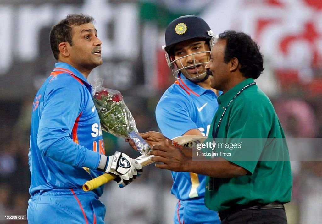 <a gi-track='captionPersonalityLinkClicked' href=/galleries/search?phrase=Virender+Sehwag&family=editorial&specificpeople=176591 ng-click='$event.stopPropagation()'>Virender Sehwag</a> of India is congratulated with flowers by a fan after scoring a double century during the 4th One Day International between India and West Indies at Holkar Stadium on December 8, 2011 in Indore, India. (Photo by Santosh Harhare/Hindustan Times via Getty Images).