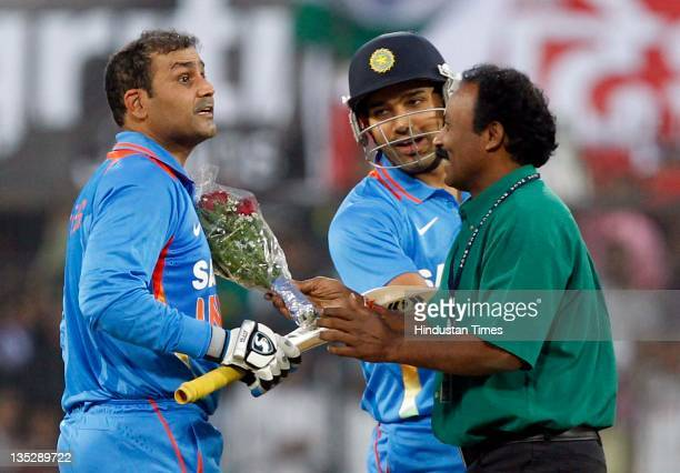 Virender Sehwag of India is congratulated with flowers by a fan after scoring a double century during the 4th One Day International between India and...